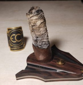half smoked cigar with long ash on top of a wooden cigar cutter