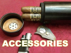 a cigar holder with 4 cigars on a red table cloth beside a wooden cigar cutter and a lighter