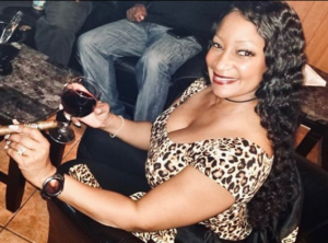 black woman smiling and holding a cigar while holding a glass of red wine