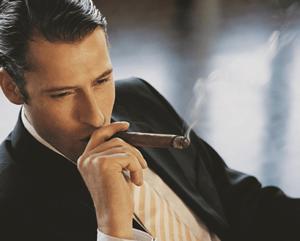 man wearing a black suit smoking cigar