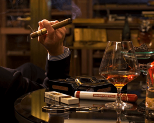 man's arm holding a lit cigar beside a table with a glass of whiskey, cigar cutter, ash tray and box of matches