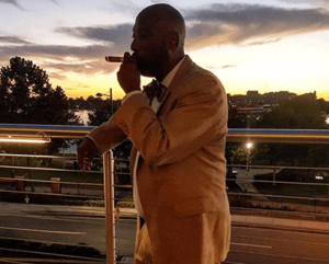 black man standing on a balcony outside wearing a yellow suit and smoking a cigar