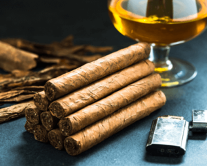A pyramid of cigars (1, 2, 3 and 4) beside a glass of whiskey and a lighter