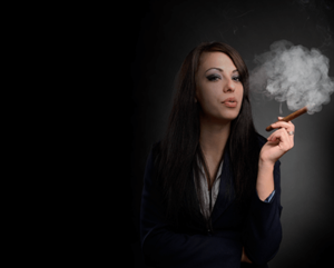 woman standing holding a lit cigar and exhaling smoke