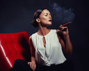 black woman sitting in a red leather chair holding a lit cigar