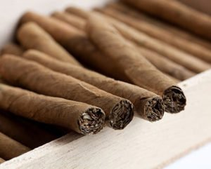 wooden box of cigars on two rows with four cigars on top