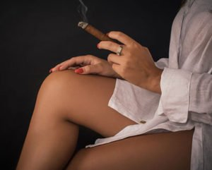 woman sitting with her hand on her thigh holding a lit cigar