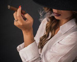 black woman with black hat smoking cigar