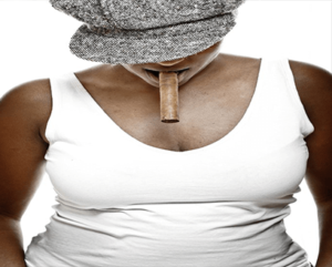 black woman standing looking down with a cigar in her mouth wearing a white tank top and grey hat