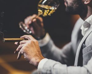 black man with beard sipping wine and holding a cigar